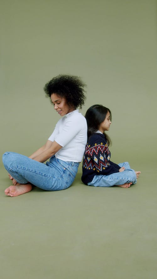 A Woman and a Girl Sitting on the Floor