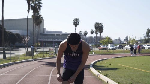 A Man Running on the Track Field