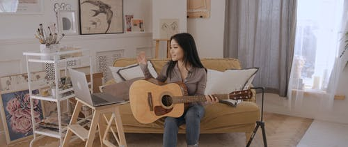 A Woman Holding a Guitar While on a Video Call