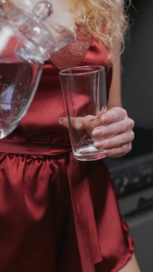 Woman Pouring Water In A Glass