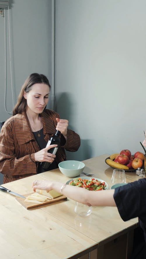 A Woman Pouring Wine on a Glass