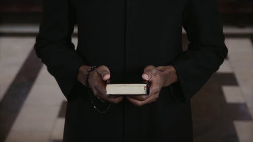 A Priest Holding a Bible and a Rosary