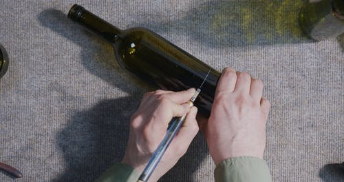 Person Cutting a Glass Bottle