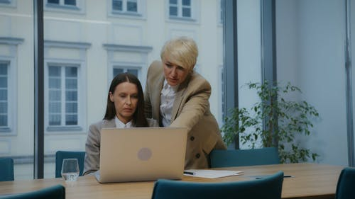 Women Looking at a Laptop in an Office
