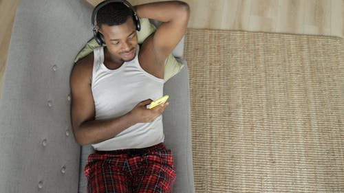 Man Lying on a Couch Listening to Music