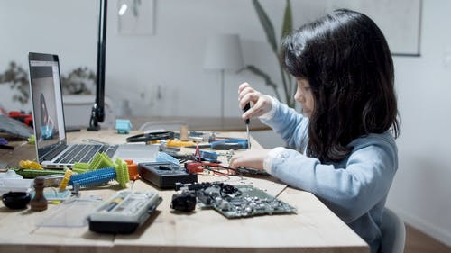 Girl Working with Computer Pieces