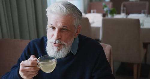 Elderly Man Talking while Sipping from a Cup
