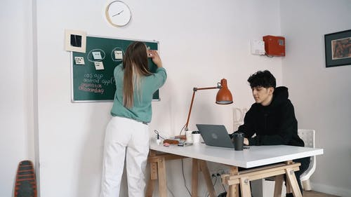 Man using Laptor while Woman Posting Sticky Notes on the Blackboard