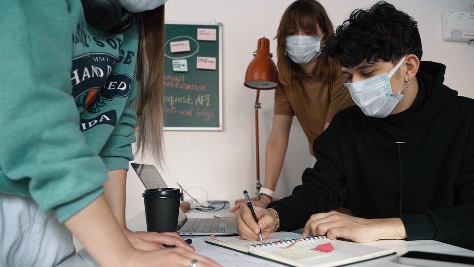 Man Wearing Face Mask Writing On A Notebook