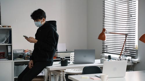 Man Sitting on His Desk while Browsing on his Phone