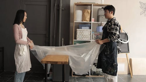 A Man and a Woman Covering a Counter with Plastic