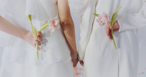 Back View of Women in Elegant Dress Holding Flowers Behind Back