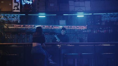 A Couple Sitting at the Bar Counter