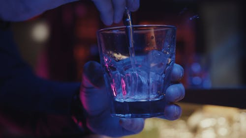 A Person Pouring an Alcoholic Beverage on a Glass