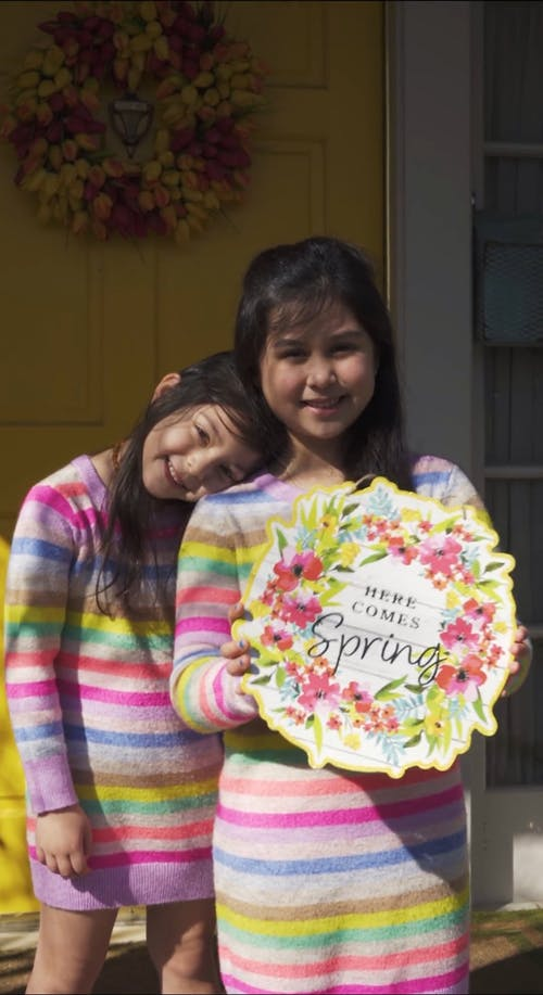 Cute Little Girls Holding a Here Comes Spring Decoration