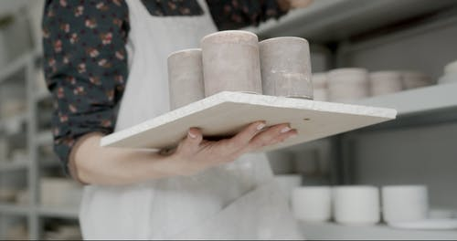 Woman Getting Ceramic Cups from Rack