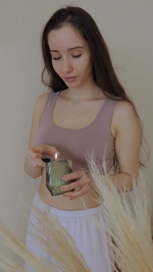 Young Woman Lighting A Candle