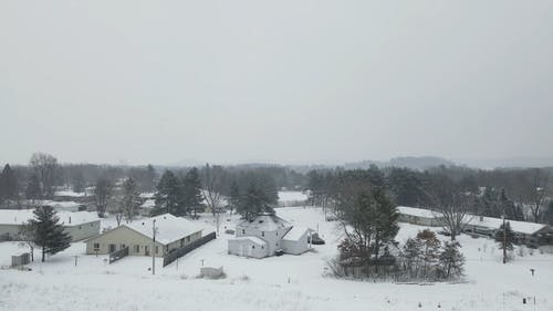 An Aerial Footage of a Snow Covered Field and Houses