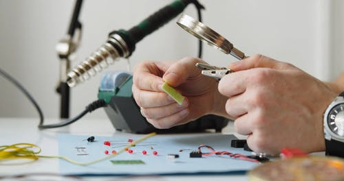 A Electrician is Working using Pliers and Magnifying Glass