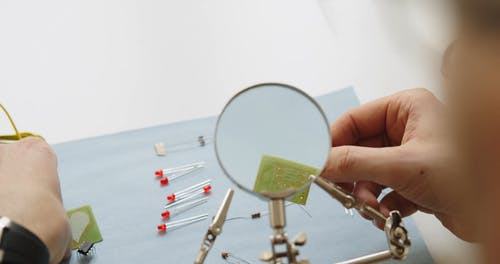 A Electrician is Working while Checking in Magnifying Glass