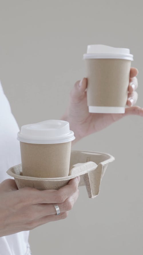Person Holding Coffee Cups in a Coffee Tray