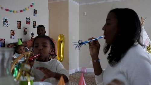 Mother And Son Playing With Party Blower