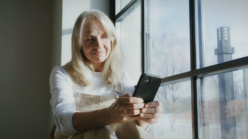 Woman Using a Smartphone by the Window