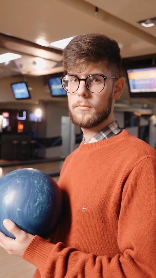 Man Holding Bowling Ball while Looking at Camera