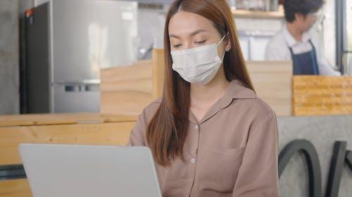 Woman using Laptop Wearing Facemask