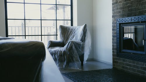 A Couch and an Armchair Covered in Plastic Sheets