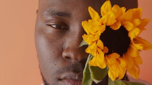 Close Up of a Man Holding a Sunflower