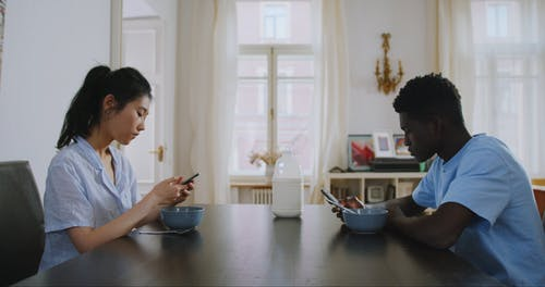 Man and Woman Focused On Using Their Smartphones