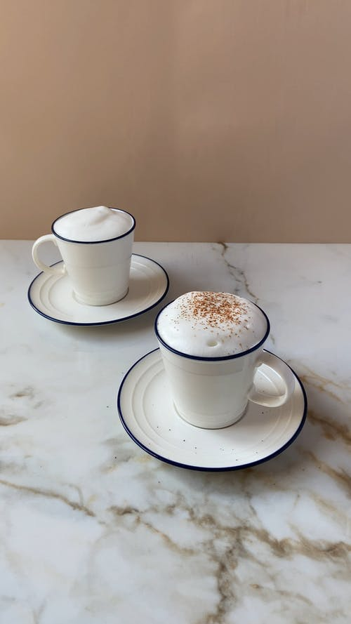 Dusting a Cups of Coffee with Cocoa Powder