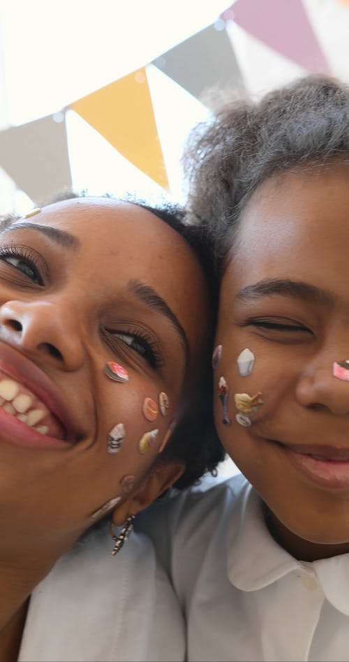 Close-Up View of Mother and Daughter with Stickers on Their Faces