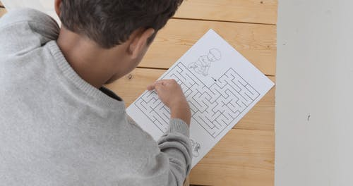 High-Angle Shot of a Kid Playing a Maze Puzzle