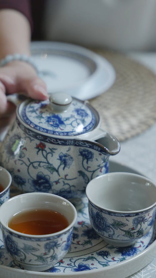 Close-Up Shot of Pouring Tea on a Teacup
