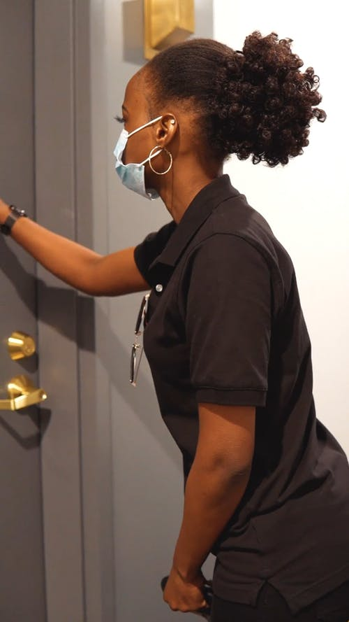 Woman Wearing Face Mask Knocking on the Door