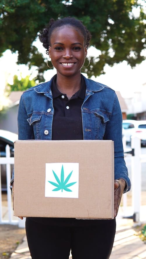 Young Woman Delivering Cannabis Shipping Box