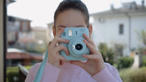 Woman Taking Photo Using an Instant Camera