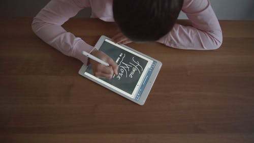 Girl Writing on a Tablet Using a Stylus