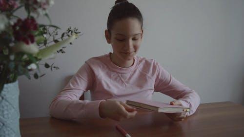Girl Opening Notebook