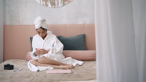 Woman Sitting on Bed while Using Cellphone