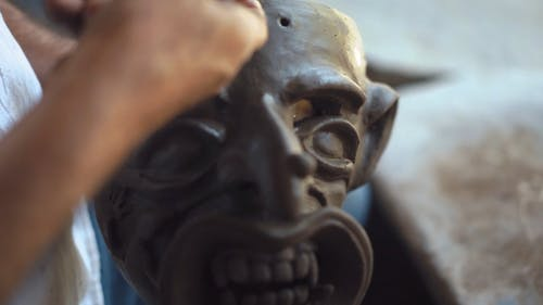 Close Up View of a Man Sculpting a Clay Mask