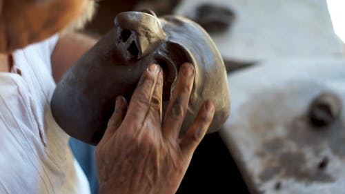 A Man Sculpting a Mask Made of Clay