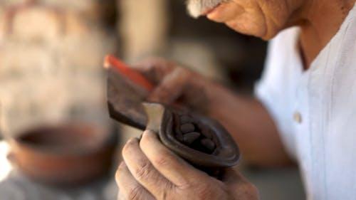 An Elderly Man Sculpting a Mask