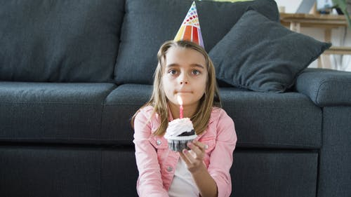 Girl Blowing the Lighted Candle on the Cupcake