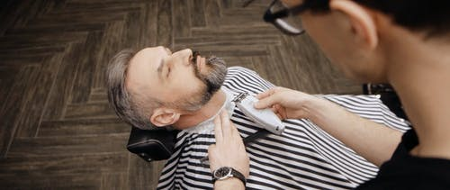Barber Trimming the Beard of the Man