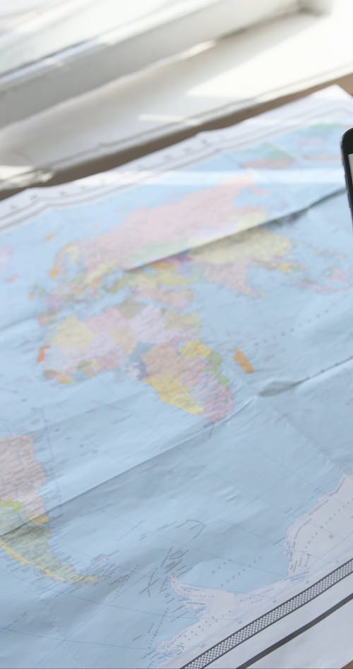 A World Map and a Person Holding a Phone