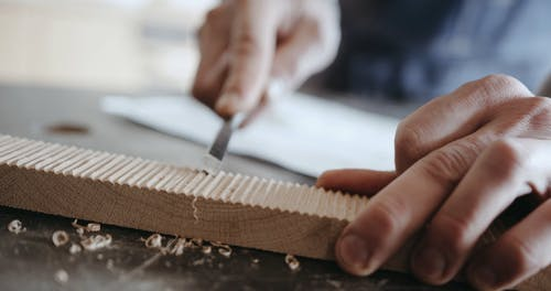 Man Carving Lines on Wood