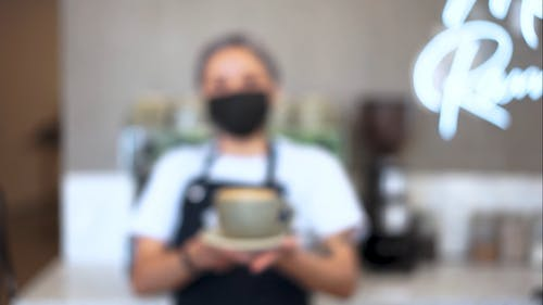 A Barista Holding a Cup of Coffee